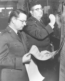 "Major Ernest J. Fawbush (left) and Captain Robert C. Miller examining weather data ca. 1948.  Data those days came in via ""high speed"" (probably about 60 wpm) teletype."